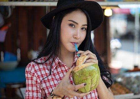Garota tomando água de coco, uma opção que faz parte de uma alimentação saudável no verão