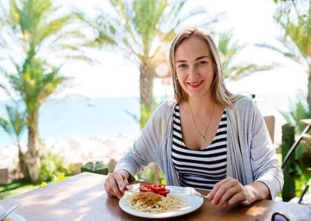 Mulher comendo macarrão à beira-mar