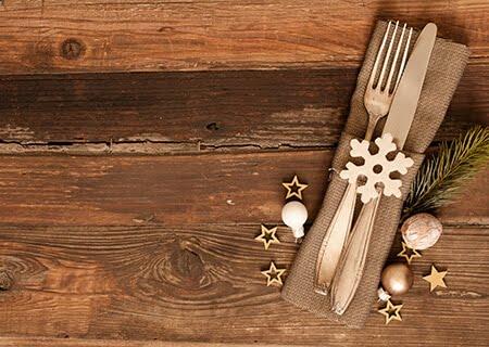 Garfo e faca sobre guardanapo de papel em mesa com lâmpada e enfeites de estrelas e neve brilhantes. Fundo foto criado por wirestock - br.freepik.com