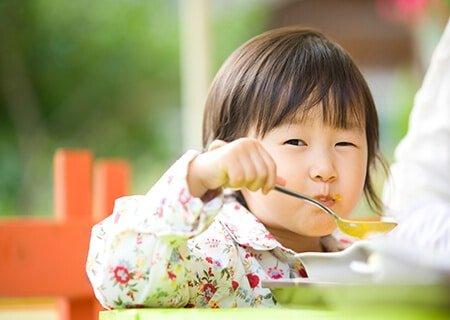 Criança comendo sopa de mandioca cremosa