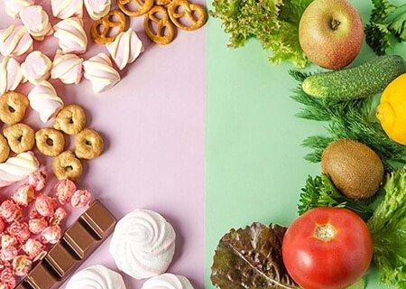 Painel dividido nas cores rosa e verde. Do lado esquerdo, rosa, alimentos industrializados como pretzels, suspiros e chocolates. Do lado direito, verde, há alimentos como alface e tomates.