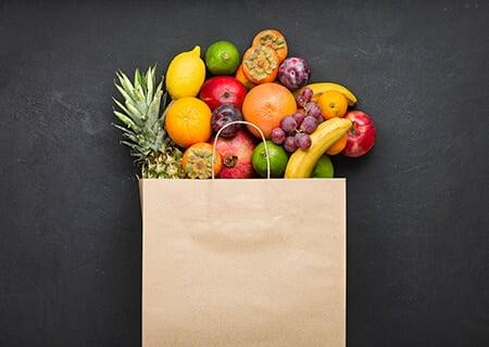 Frutas saindo de sacola de papelão