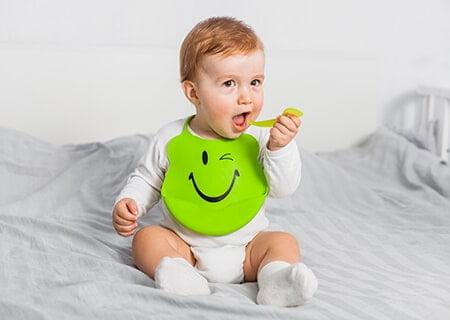 Bebê sentado na cama levando colher à boca