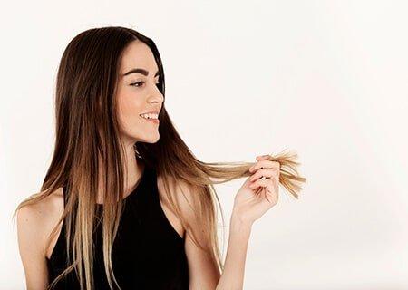 Menina sorridente segurando seu cabelo