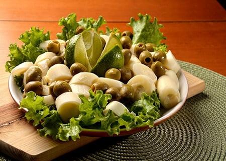 Salada de alface, azeitonas sem caroço e palmito em fatias, com pedaços de limão ao centro