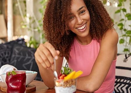 Mulher sorrindo comendo iogurte