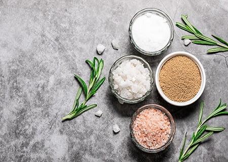 Diversos tipos de sal de cozinha distribuídos em potes