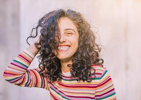 Mulher sorrindo com as mãos nos cabelos ondulados