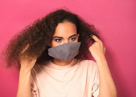 Mulher tirando máscara no rosto