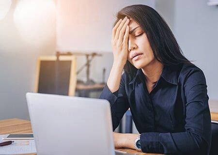 Mulher sentada em frente a computador com a mão na testa