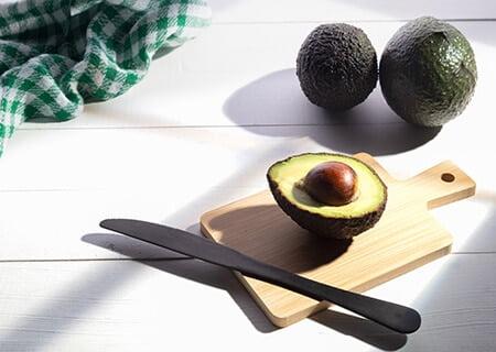 Abacates em cima de mesa. Um está fatiado sobre tábua, com faca ao lado e pano xadrez ao fundo
