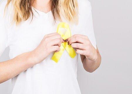 Mulher segurando laço amarelo no peito
