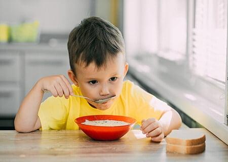 Menino sentado à mesa e comendo na tigela