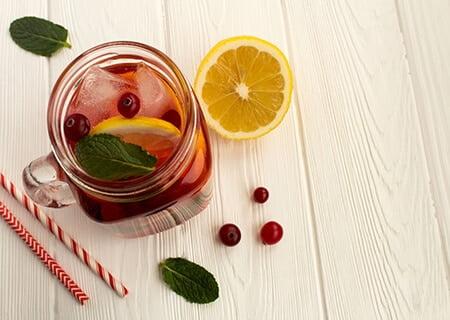 Suco de cranberry em copo de vidro sobre mesa ao lado de fatia de laranja, folhas e canudos