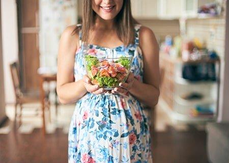 Mulher grávida segurando pote de salada