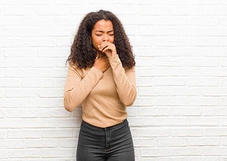 Garota com a mão no pescoço e na boca, tossindo