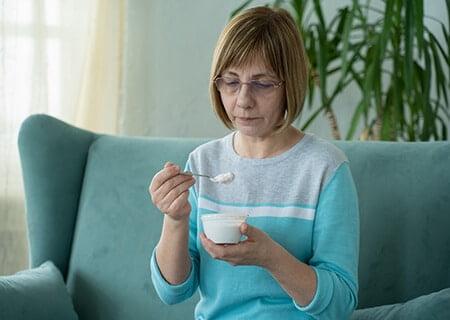 Mulher sentada no sofá comendo iogurte