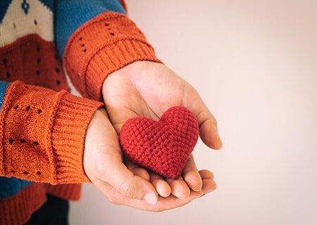 Mão segurando miniatura de coração de crochê