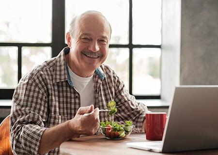 Homem idoso comendo salada e sorrindo