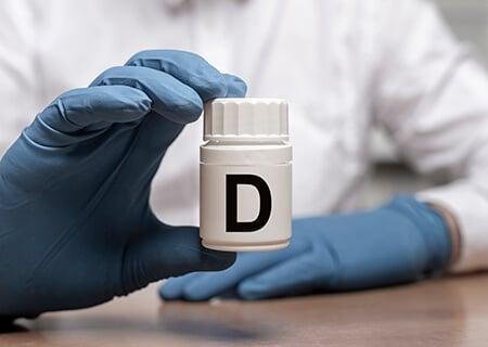 Pessoa com luvas segurando frasco de vitamina D