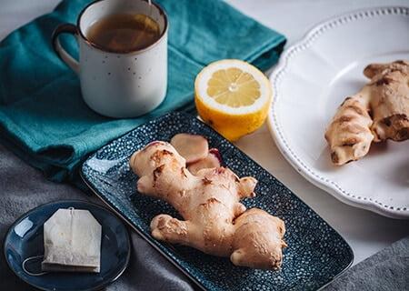 Gengibre em prato ao lado de xícara com chá e uma rodela de limão na mesa