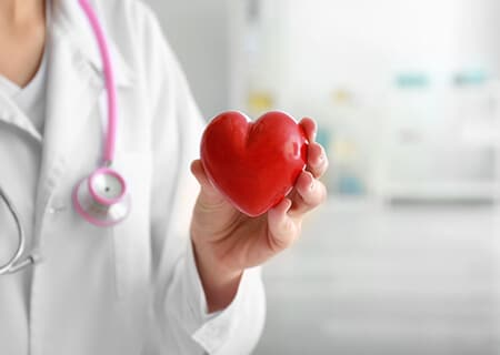 Médica segurando coração de borracha