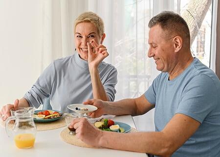 Mulher e homem sentados à mesa segurando suplementos