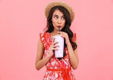 Mulher tomando bebida em copo de plástico