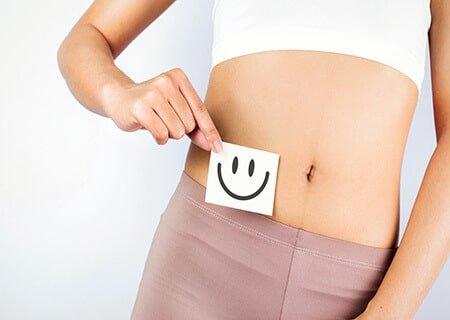 Pessoa segura papel com rosto feliz em frente à barriga
