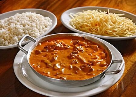 Strogonoff sem lactose em prato ao lado de prato de arroz e outro de batata palha
