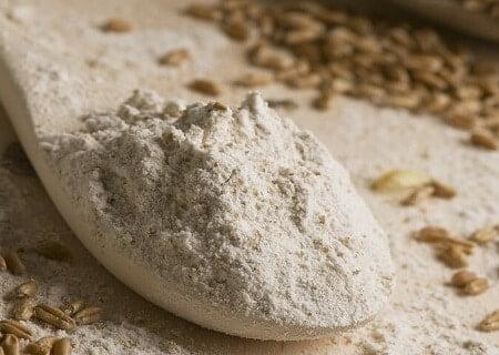 Colher de pau com farinha de centeio e outra com grãos de centeio