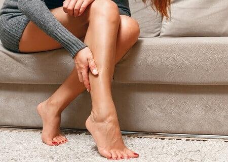 Mulher sentada com as mãos nas pernas