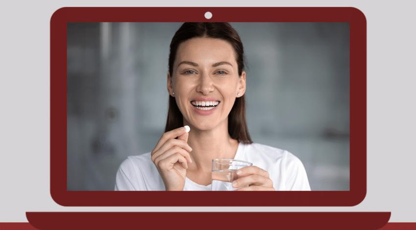 Mulher ingerindo um suplemento com um copo de água em uma das mãos