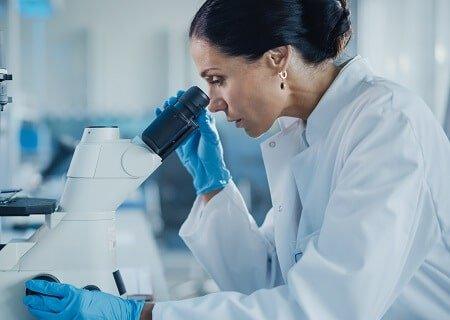 Mulher observando um experimento pelo microscópio