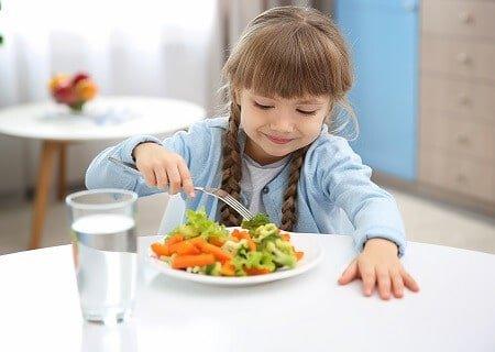 Menina comendo prato de legumes